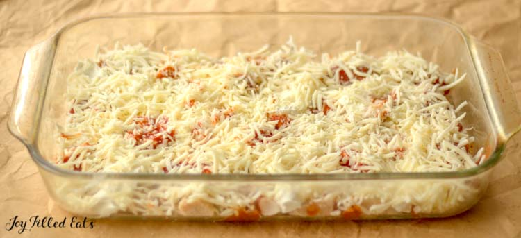 chicken pizza casserole in dish before baking topped with shredded cheese