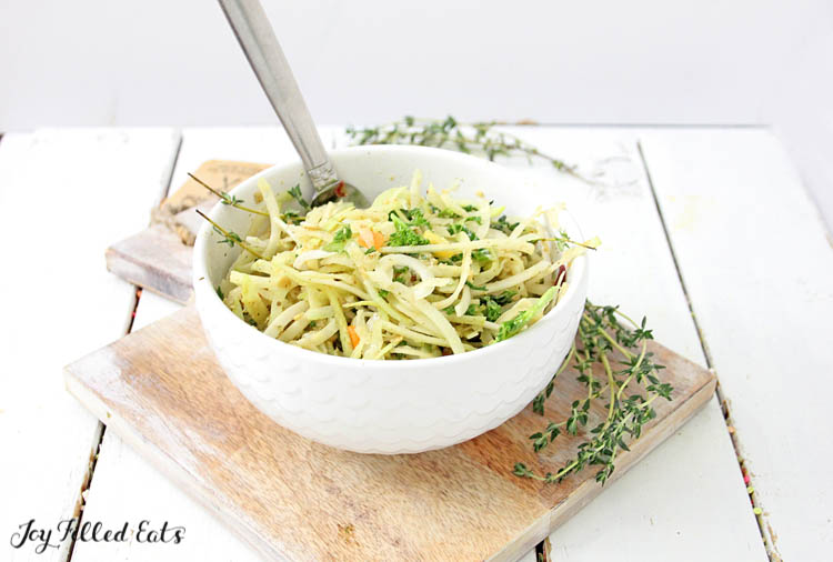 kohlrabi salad with homemade Italian dressing in white bowl with fork set on a cutting board