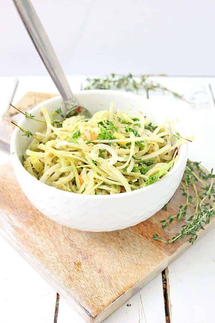 kohlrabi salad with homemade Italian dressing in white bowl with fork close up set on a cutting board