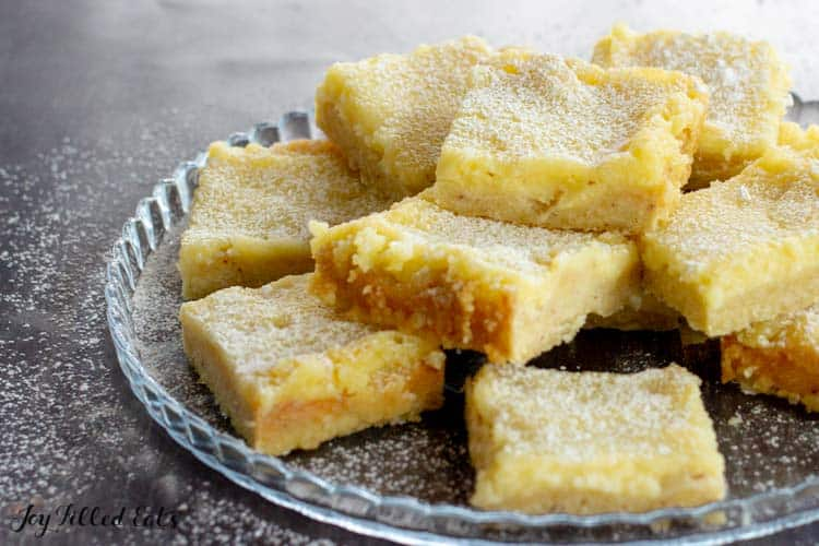 pile of lemon squares on a glass plate