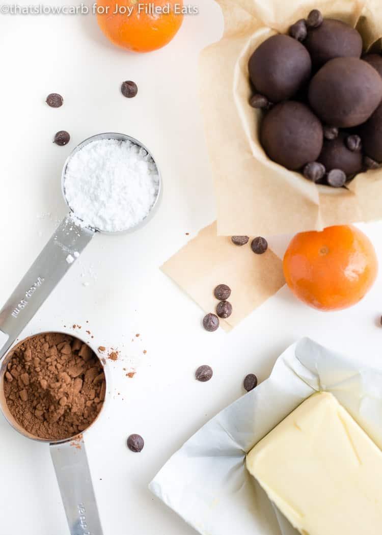 individual ingredients for orange fudge fat bombs next to a bowl of orange fudge fat bombs