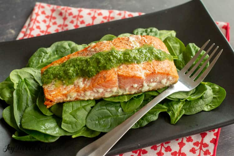 a black plate with salmon from the pesto salmon recipe on top of a bed of baby spinach