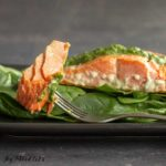 fork with salmon piece resting on plate of baby spinach with a salmon filet topped with pesto close up