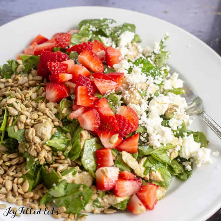 baby spinach salad topped with diced strawberries, feta cheese and sunflower seeds in a shallow bowl with fork