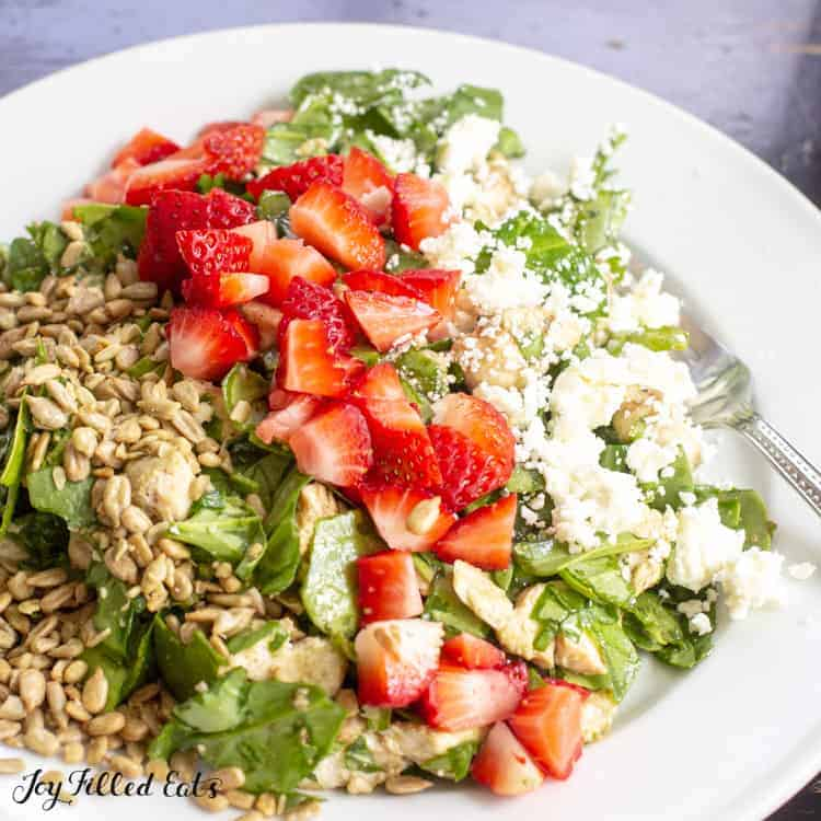 baby spinach salad topped with diced strawberries, feta cheese and sunflower seeds close up