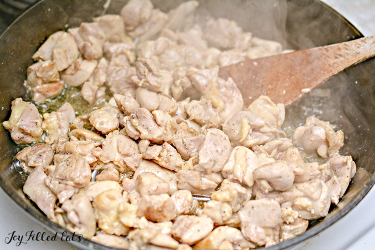 chicken pieces cooking in skillet with wooden spoon