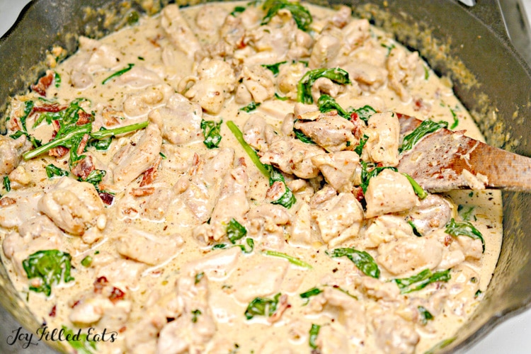 skillet full of cooking chicken carbonara with wooden spoon