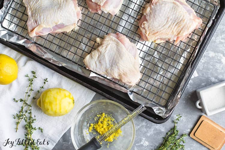 raw chicken thighs placed on aluminum lined sheet pan next to bowl of lemon zest along with other ingredients