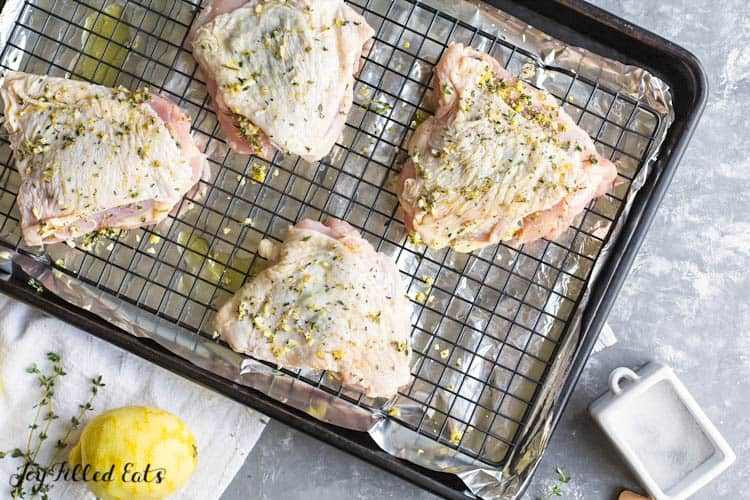 marinaded chicken thighs placed on aluminum lined sheet pan