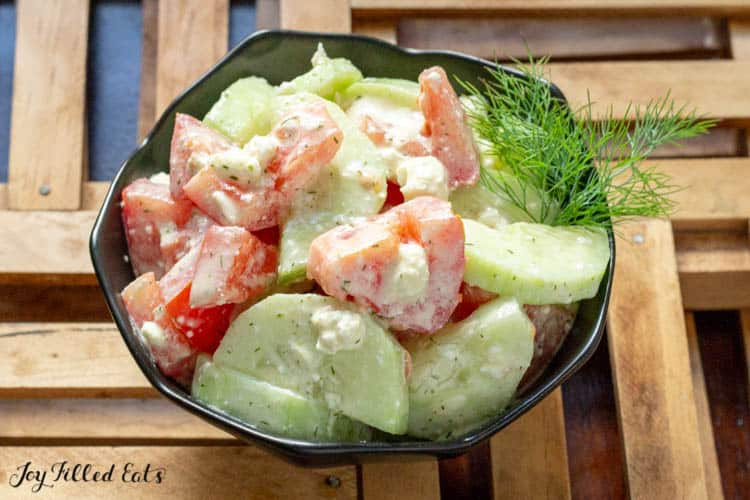 bowl of cucumber and tomato salad garnished with fresh dill close up