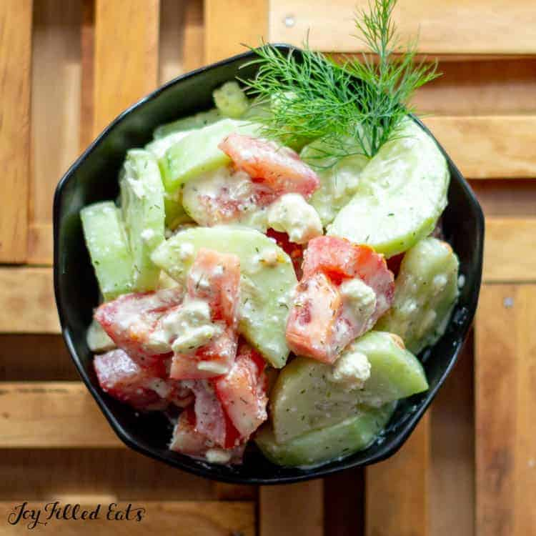 overhead shot of cucumber tomato salad in a black bowl topped with dill