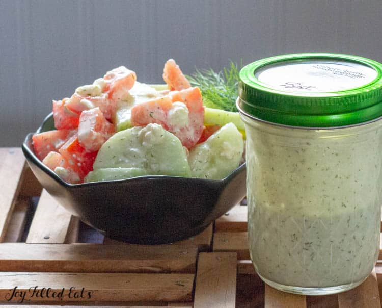 small black bowl of cucumber and tomato salad next to a mason jar of dressing