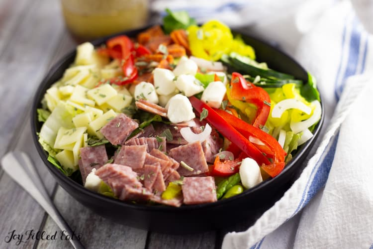 Italian salad topped wtih meats, cheeses, and vegetables in a black bowl