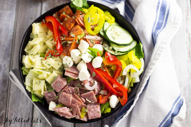 antipasto salad topped with peppers and mozzarella