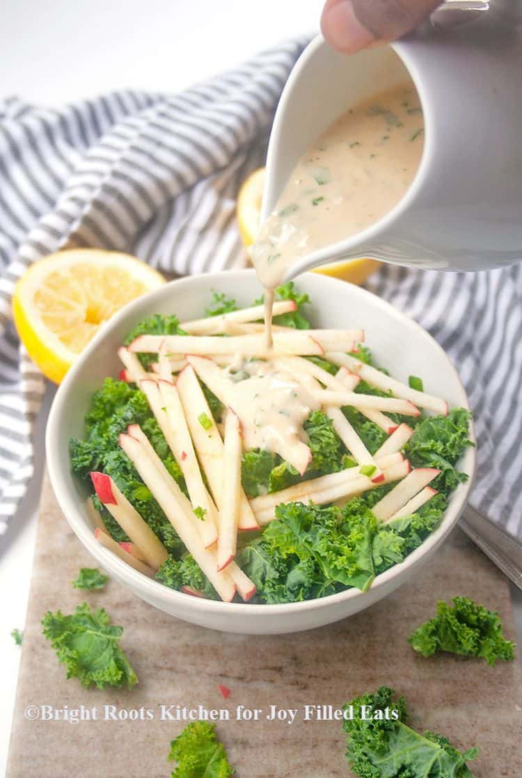 hand pouring pitcher of tahini dressing onto kale and apple salad