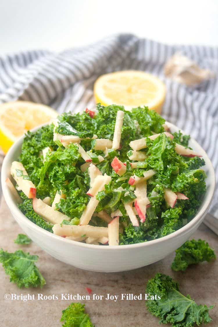 kale salad with apples in bowl surrounded by lemon halves