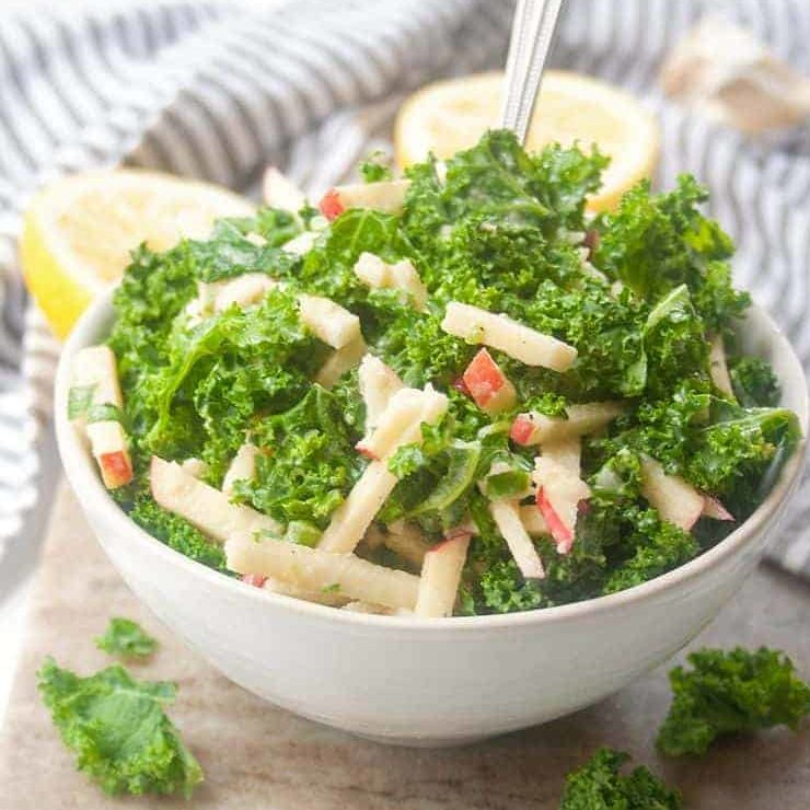 kale salad with matchstick sliced apples in white bowl