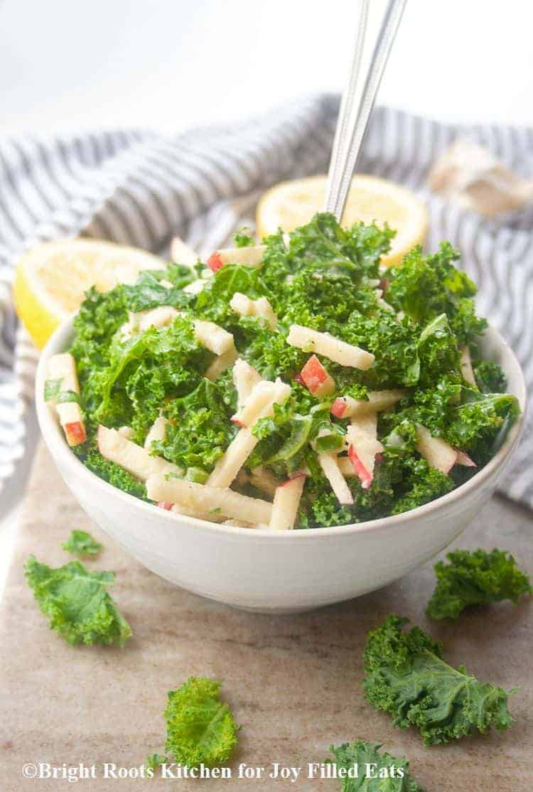 kale salad with apples and tahini dressing in a white bowl with a fork