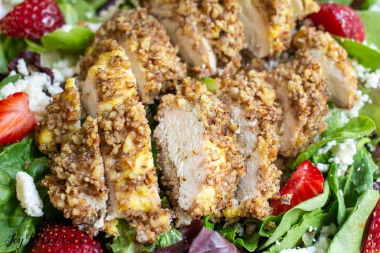 close up of a sliced pecan crusted chicken tender on salad