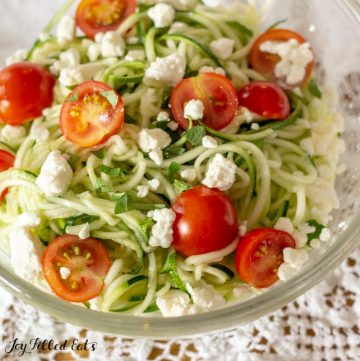 glass bowl of zucchini noodle salad topped with tomatoes and feta cheese on a white lace tablecloth