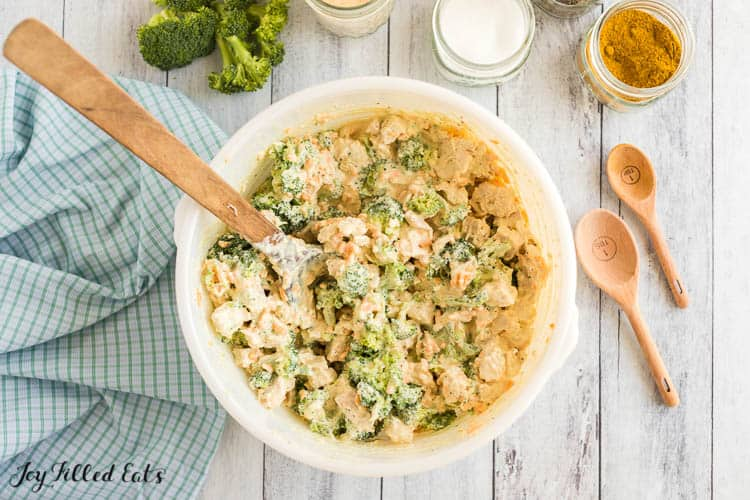 chicken and broccoli in sauce in a large bowl with a wooden spoon