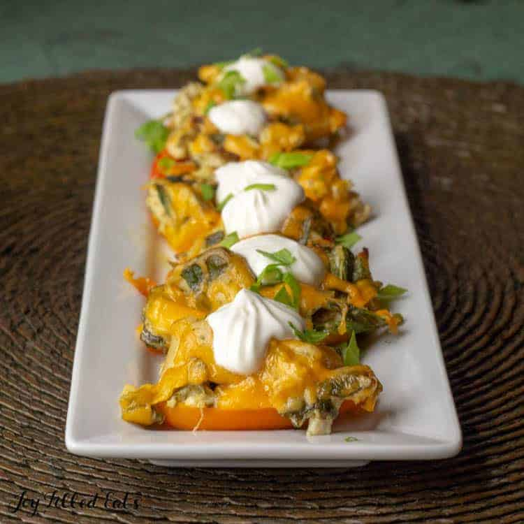 chicken stuffed peppers on a white platter topped with sour cream