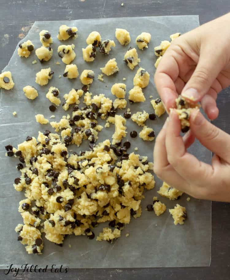 hand breaking apart cookie dough into small pieces set onto parchment paper