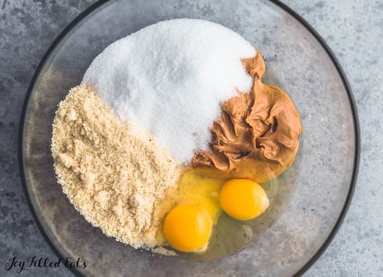 a glass bowl with peanut butter, eggs, almond meal, and erythritol