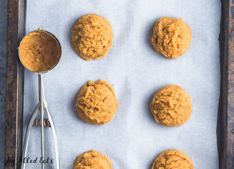 a cookie scoop and scoops of batter on a parchment lined baking sheet