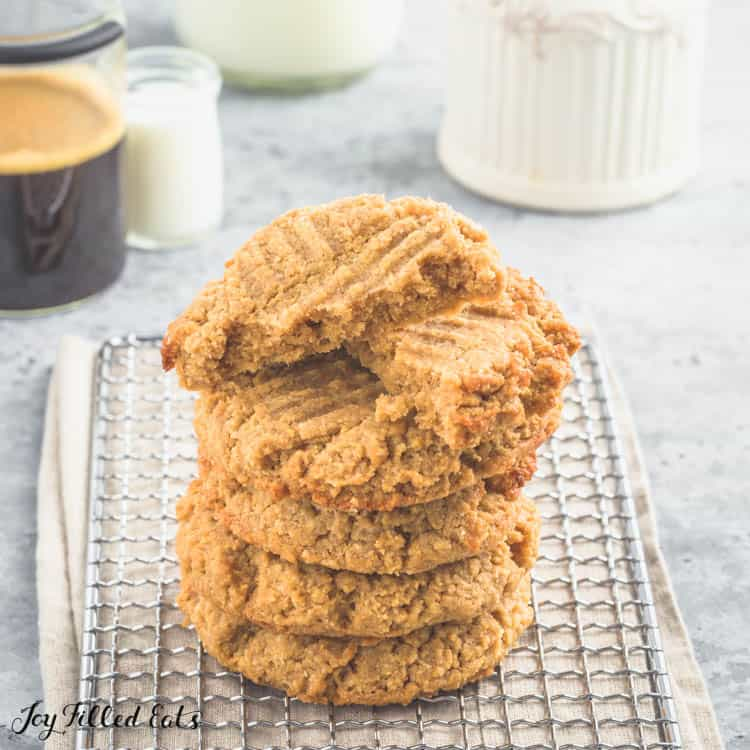 Peanut Butter cookies stacked on a drying rack with top cookie cut in half