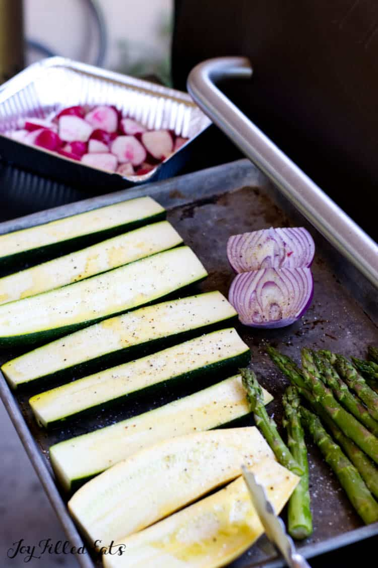 sliced zucchini, asparagus, and red onions on a tray