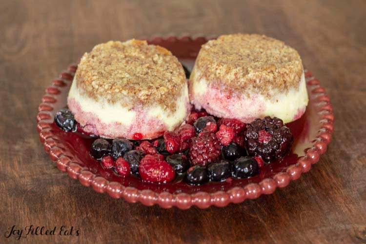 red bowl of mixed berries topped with two individual cheesecakes crust side up