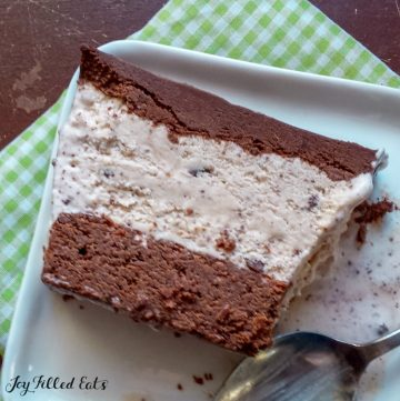 Slice of Mint Chocolate Chip Ice cream cake on a white plate with spoon