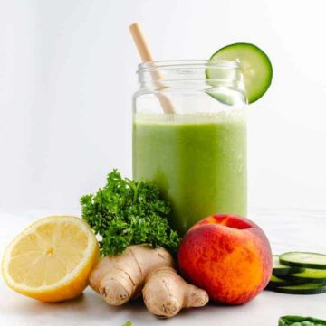 glass of green smoother with paper straw and cucumber slice surrounded by fresh ingredients