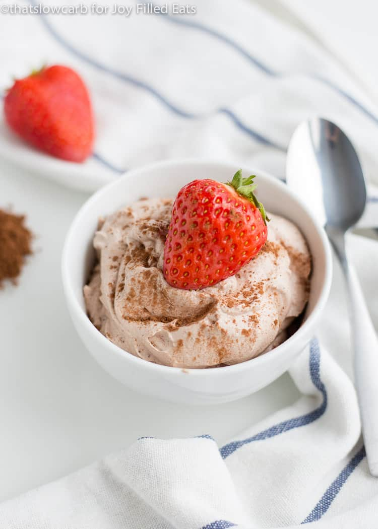 Chocolate Whipped Cream in a small white bowl topped with a strawberry