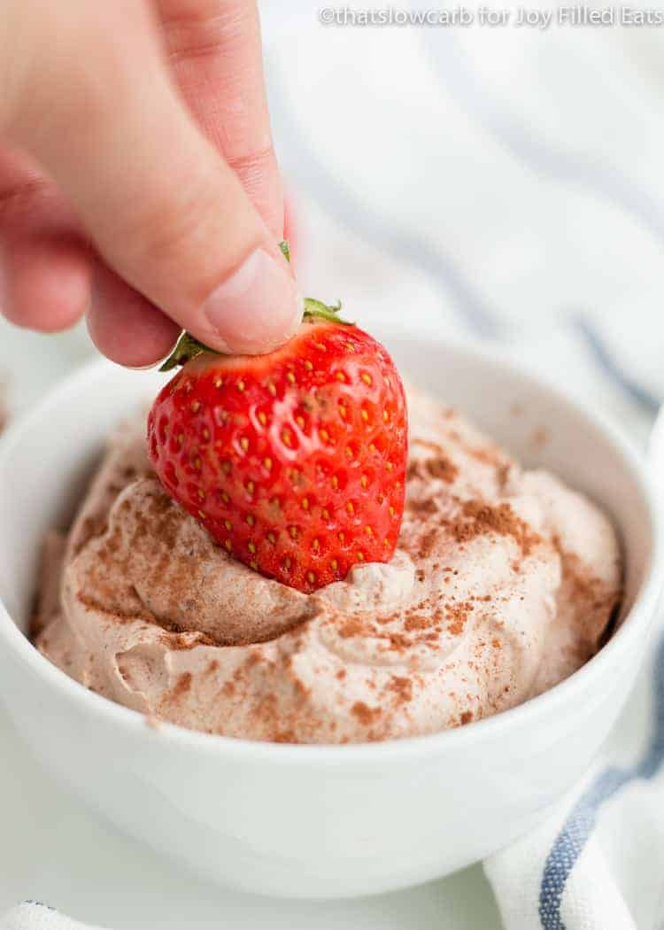 a hand dipping a strawberry into the Chocolate Whipped Cream