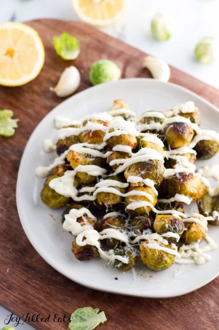 grilled brussel sprouts piled up on a white plate
