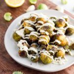 grilled Brussels sprouts on a white plate drizzled in lemon aioli set on a cutting board close up