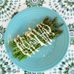 grilled asparagus drizzled in sauce and sesame seeds on a blue plate set on a decorative table cloth