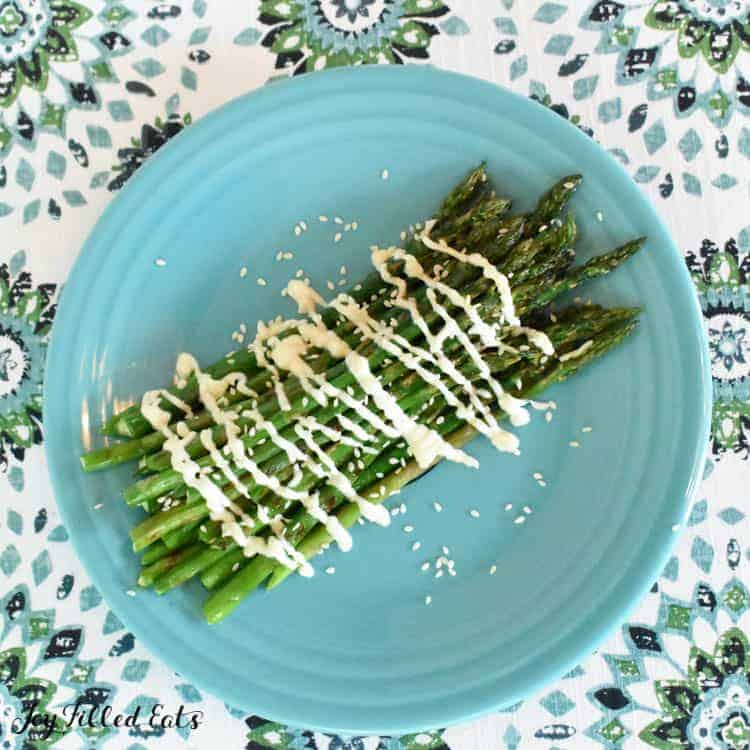 plate of grilled asparagus with sesame sauce