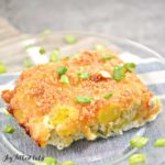 slice of yellow squash casserole on plate topped with chopped green onions close up