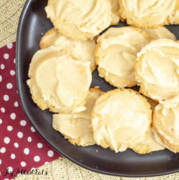 Frosted keto Vanilla Cookies on black plate