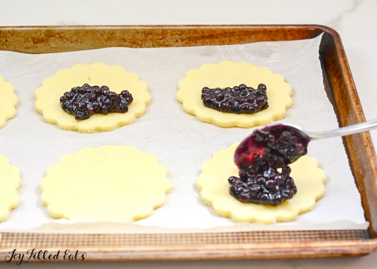 spoon placing blueberry filling onto turnover dough placed on a sheet pan