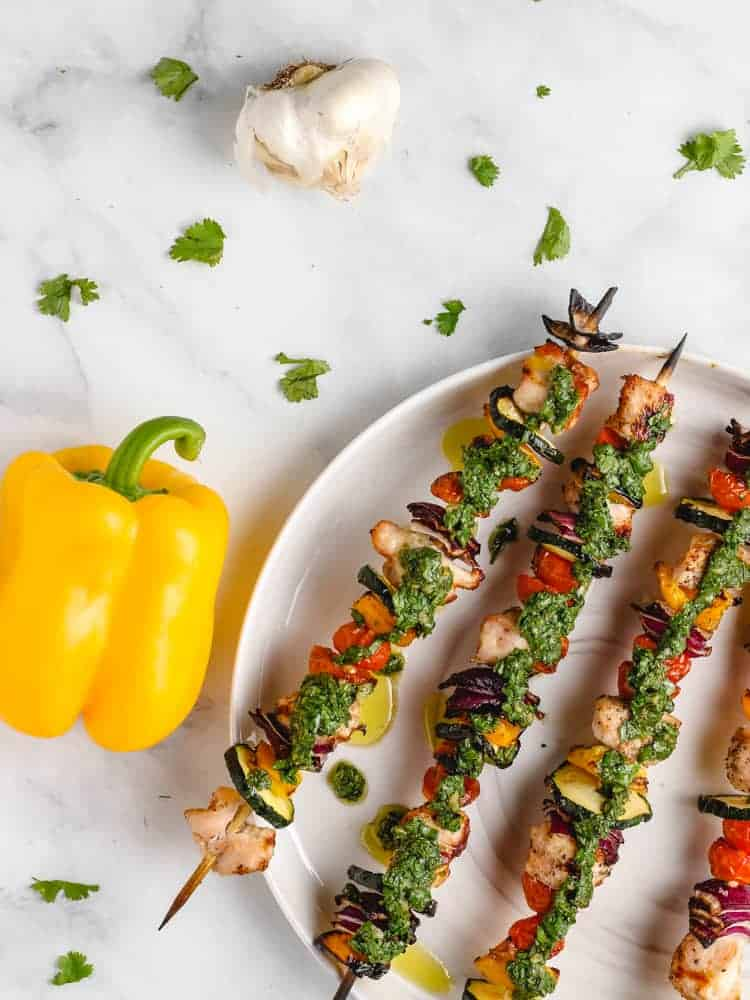 chimichurri chicken kebabs on a plate next to a yellow bell pepper and garlic bulb from above