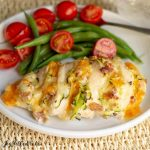 Close up of Four Cheese Bacon Hasselback Chicken plated with green beans and tomatoes on white plate