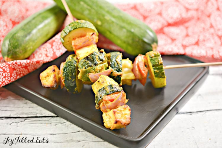 paneer tikka skewers on a black plate next to two zucchinis
