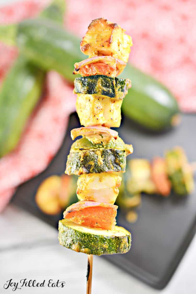 a wooden skewer with paneer cheese and vegetables
