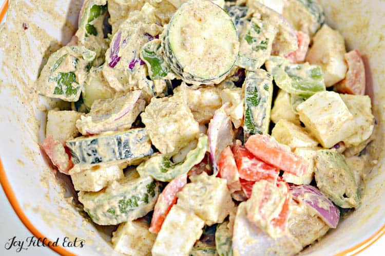 mixing bowl of vegetables and paneer in seasoning close up