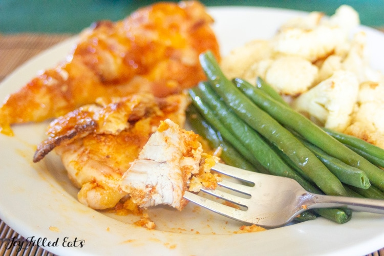 bite of chicken on a fork resting on a plate full of more chicken, green beans and cauliflower