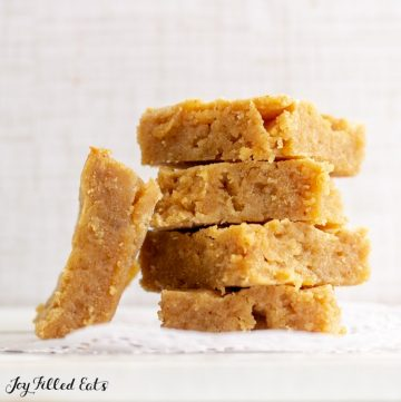 Stack of White Chocolate Peanut Butter Blondies with one upright on the side
